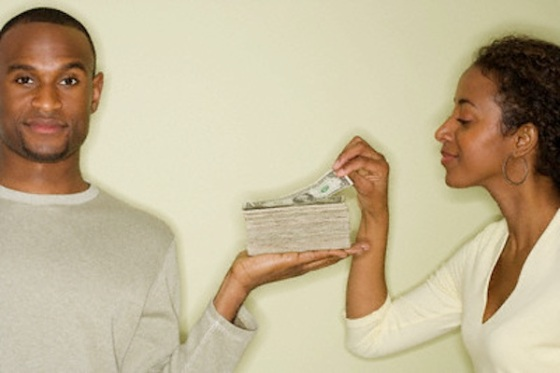 Woman taking money from stack in husband's hand --- Image by © Tetra Images/Corbis
