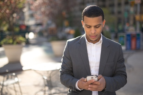 Young African American black Latino man texting cellphone - OpinionatedMale.com